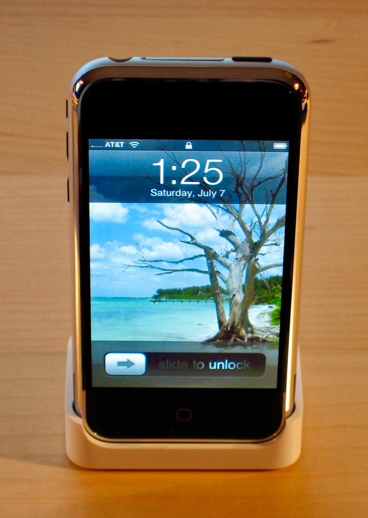Original iPhone sitting in a dock on a desk