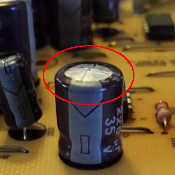 Photo of a bulged capacitor on a motherboard