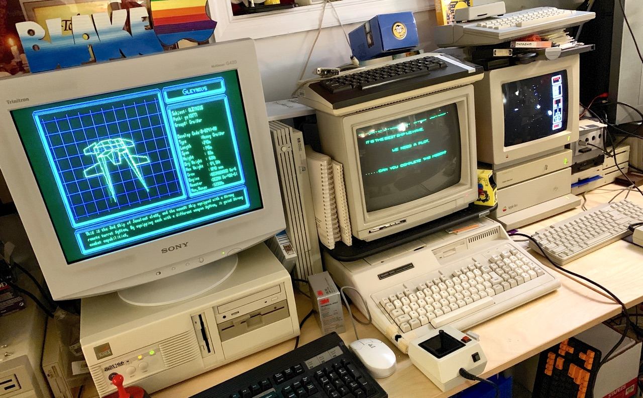 Photo of desk with two DOS PCs and an Apple IIgs, all running Silpheed